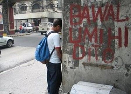 Man urinating beside a bawal umihi dito sign in the Philippines