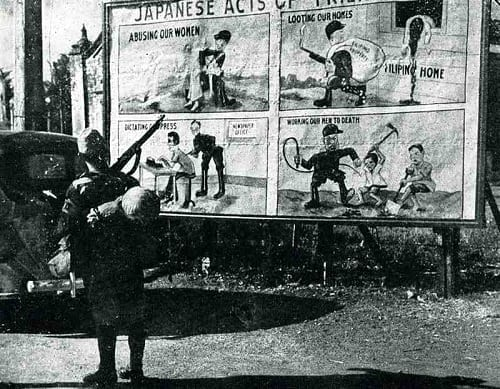 A Japanese soldier stand in front of US propaganda, in the Philippines