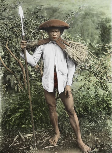 A Tinggian tribesman wears a waterproof cape made of plaited straw.