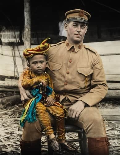 A young Moro boy sits on the knee of an American lieutenant