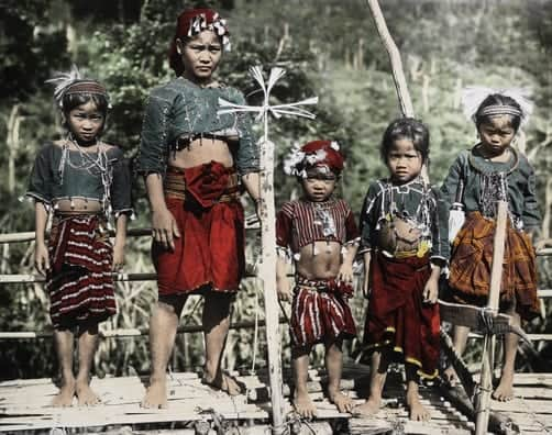 Ilongot woman and girls pose on a bamboo platform